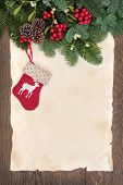 Christmas stocking decoration with winter greenery border over parchment and oak background.