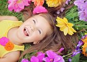 Smiling, happy little summer girl laying on the grass field with flowers