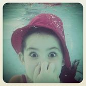 fun instagram of young girl holding breath underwater