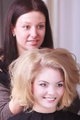 Smiling Girl With Blond Wavy Hair By Hairdresser In Beauty Salon