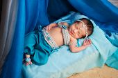 picture of belly-dance  - Sleeping six day old newborn baby girl smiling and wearing a blue belly dance costume - JPG
