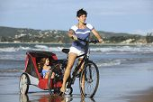 Mother and daughters riding a bike on the beach.