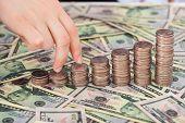 Fingers Walking Up Coinstack On Dollar Bills