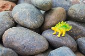 picture of giant lizard  - Plastic dinosaur toy on pebble stone background - JPG