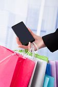 Businesswoman With Smartphone And Shopping Bags