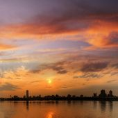 Panoramic cityscape of sunset scenery with building silhouette and river reflection under dramatic s