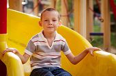 Attractive Little Boy On A Slide In A Playground
