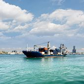 Freighter with cargo sailing on sea with blue sky and green water and beautiful cityscape of buildin
