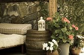 pic of bunk-bed  - A vintage photo of a garden with an old wooden bed, icon-lamp, flowers and an old wooden barrel