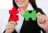 Happy Businesswoman Holding Puzzle Pieces