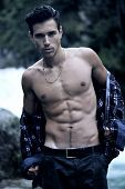 Handsome Young Man Near Mountain Waterfall With Open Shirt