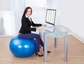 stock photo of pilates  - Side view portrait of businesswoman using computer while sitting on pilates ball in office - JPG