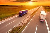 stock photo of travel trailer  - Blue and white truck in motion blur on the highway at sunset - JPG