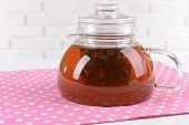Teapot with tea on table on brick wall background