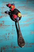 Ripe sweet different berries in vintage spoon, on old wooden table