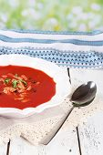 Tasty tomato soup with croutons on table on natural background