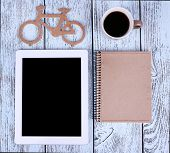 Tablet and mug of coffee on wooden background