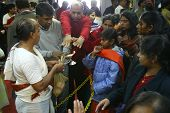 NEW YORK - JANUARY 1:  Hindu faithful reach out to touch a small flame as they pray for tsunami vict