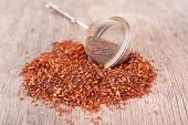 Dried rooibos tea in tea-strainer on wooden table