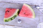 Slices of watermelon on cutting board on wooden background