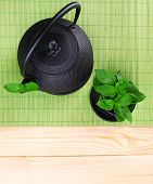 Chinese traditional teapot with fresh mint leaves on wooden background