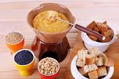 Fondue, little bowls of spice, rusk and biscuits on cutting board on wooden background