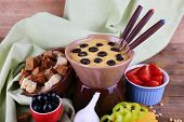 Fondue, olives, tomatoes, rusks and spices on napkin on wooden background