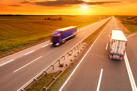 image of trucks  - Blue and white truck in motion blur on the highway at sunset - JPG