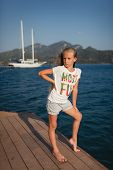 The portrait in full length of the young girl with mountain and yacht behind her.