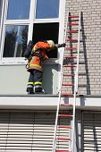 picture of firefighter  - A firefighter must enter the house through the window when using - JPG