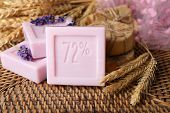 Bars of natural soap on wicker mat, on light background