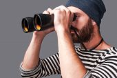 stock photo of binoculars  - Side view of confident young bearded man in striped clothing looking through binoculars while standing against grey background - JPG
