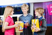 Portrait of smiling boy holding popcorn while standing with siblings at cinema
