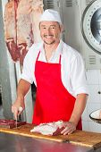 Portrait of happy male butcher with red meat at butchery