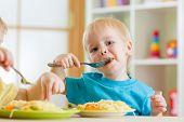 kid boy eating spaghetti in nursery