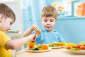 image of kindergarten  - children eating vegetables in kindergarten or at home - JPG