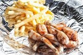 stock photo of gril  - Tasty fries with grilled chiken on foil - JPG