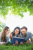 Happy students using tablet pc outside at the university