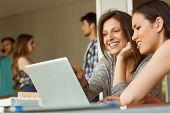 Smiling friends sitting using laptop near classmates at school
