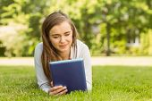 University student lying and using tablet pc in park at school