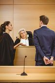 foto of court room  - Judge and lawyer listening the criminal in handcuffs in the court room - JPG