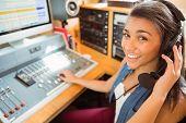 Smiling university student mixing audio in the studio of a radio