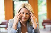 Blonde businesswoman getting a headache in office building