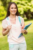 Portrait of a smiling student with a shoulder bag and holding book in park at school