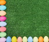 Two crossing lines of painted eggs making corner on green grass