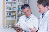 Man holding medication and his colleague writing a prescription in the pharmacy