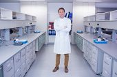 Portrait of a smiling biochemist standing with arms crossed in laboratory