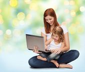 childhood, parenting and technology concept - happy mother with adorable little girl and laptop computer over green lights background