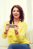 home, technology and internet concept - smiling woman playing with smartphone sitting on couch at home