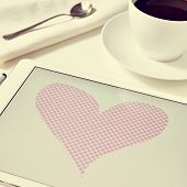 a heart drawn in a graphics editor of a tablet on a table set for breakfast